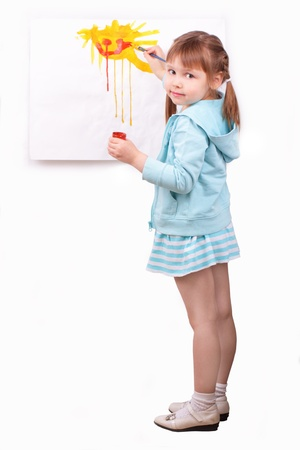 Little girl paints a picture photo