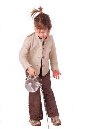 Little girl pours from a jug photo