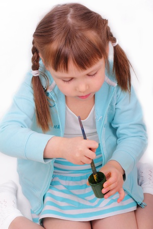 Little girl stirs the paint with a brush Stock Photo - 13090628