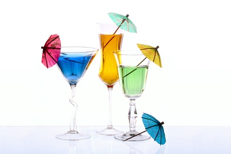 Three wineglasses are filled with colored beverages and four cocktail umbrellas