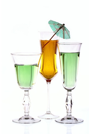 Three wineglasses are filled with colored beverages Stock Photo