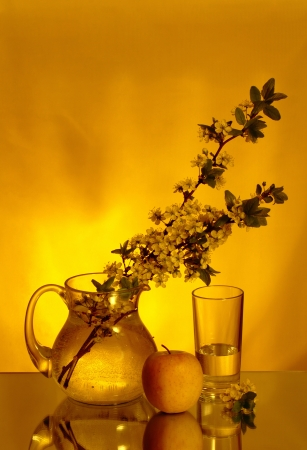 Creative composition with glass, jug, apple and flowers photo