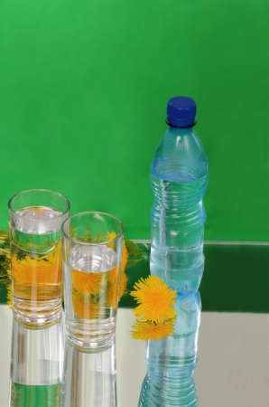 Yellow dandelion flowers, glasses and bottle photo