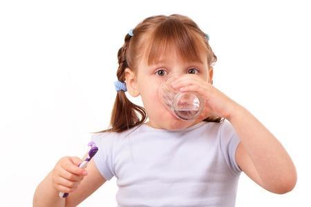 Kislány a fogkefével vizet iszik a pohár