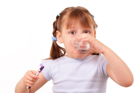 Little girl with a tooth brush drinks water from the glass