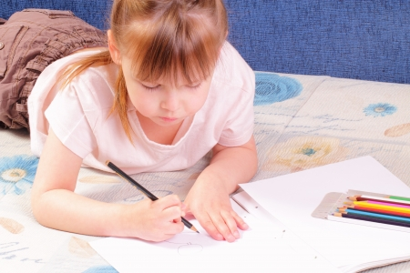 Beautiful little girl draws picture photo