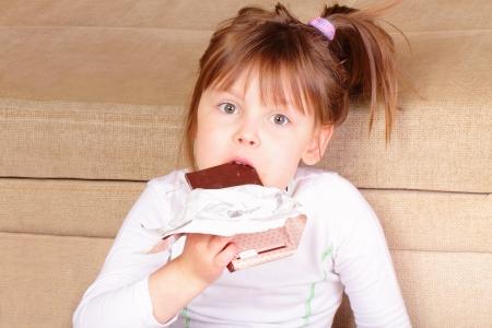 Beautiful little girl eating chocolate photo