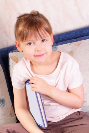 Beautiful little girl sitting with book photo