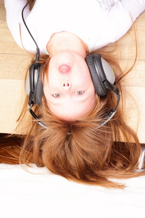 Funny little girl upside down with headphones Stock Photo