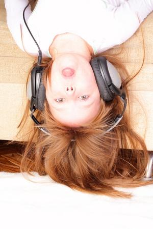 Funny little girl upside down with headphones Stock fotó
