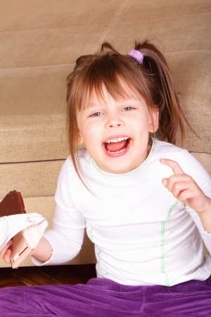 salubrious: Happy little girl eating chocolate