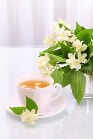 Cup of tasty jasmine tea and flowers photo