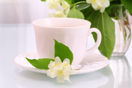 White cup and jasmine flowers photo
