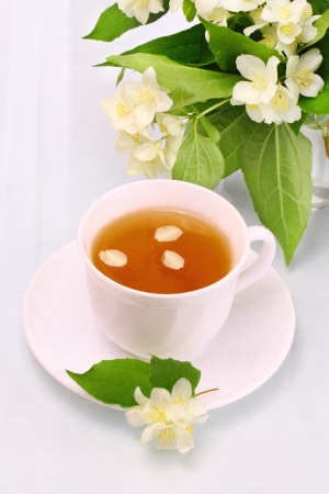White cup with jasmine tea and flowers photo