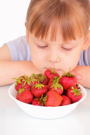 Beautiful little girl and a white soup plate with strawberries photo