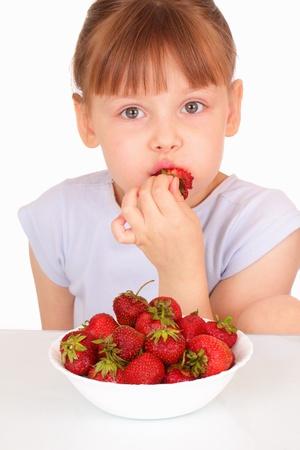 Beautiful little girl eating tasty strawberries photo
