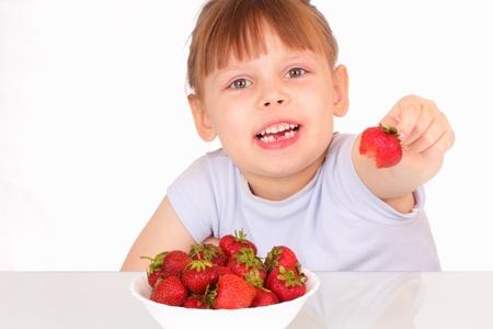 Beautiful little girl gives strawberry photo