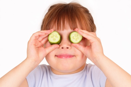 Funny little girl with pieces of cucumber photo