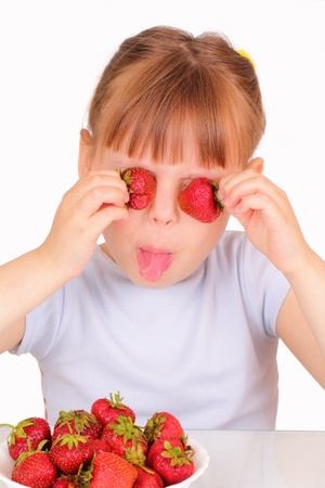 Funny little girl with tasty strawberries photo