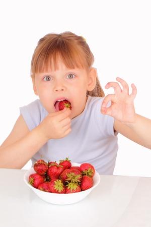 Pretty little girl eating strawberries photo