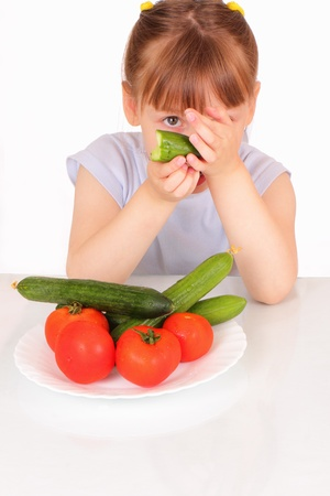 Pretty little girl with a white plate with cucumbers and tomatoes photo
