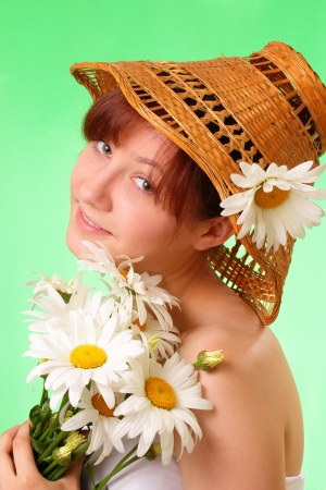 Beautiful young girl in the hat with chamomile flowers photo