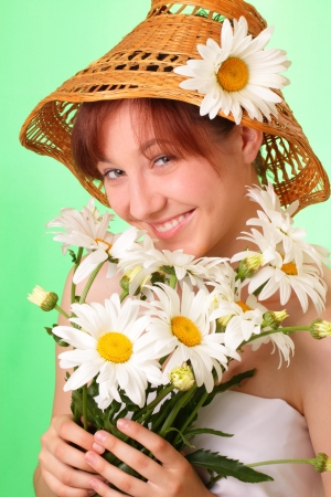 Funny young girl in the hat with chamomile flowers photo