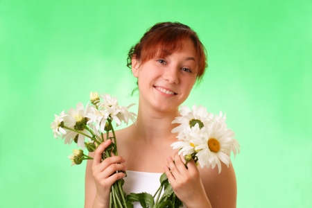 Funny young girl with chamomile flowers photo