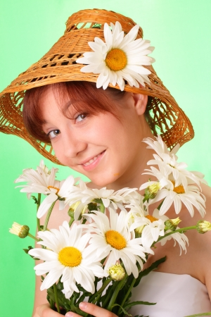 Pretty young girl in the hat with chamomile flowers photo