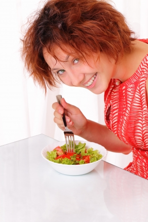 Beautiful young girl eating tasty salad
