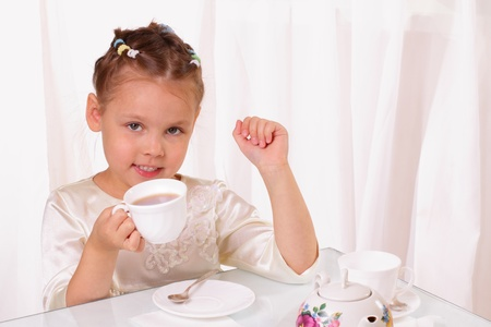 Pretty little girl drinking tea photo