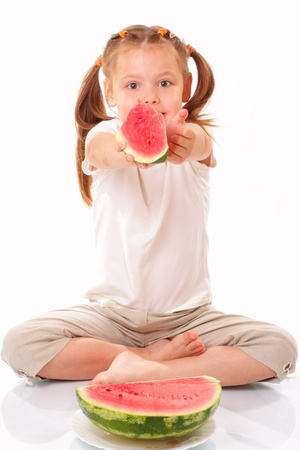 Attractive little girl gives a piece of watermelon Stock Photo