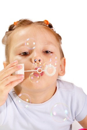 Beautiful little girl blowing soap bubbles photo