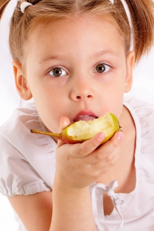 Attractive little girl eating pear