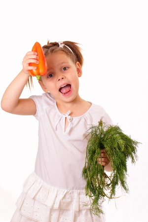 sincere girl: Funny little girl with sweet pepper and dill in her hands