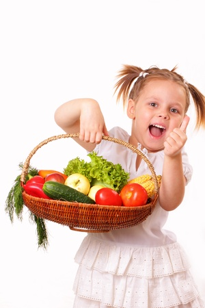 Happy little girl with vegetables and fruits photo