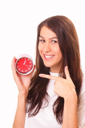 Smiling young brunette woman with alarm clock photo