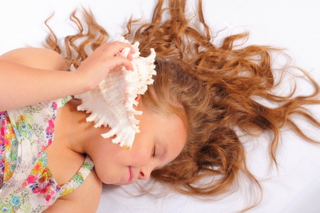 Attractive little girl with seashell