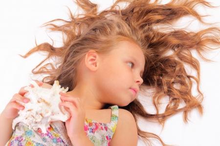 Calm little girl with seashell Stock Photo