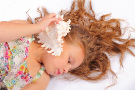 Relaxing little girl with seashell