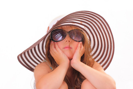 Beautiful little girl in a hat and with sunglasses Stock Photo