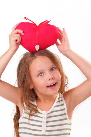 Smiling little girl with a red heart photo