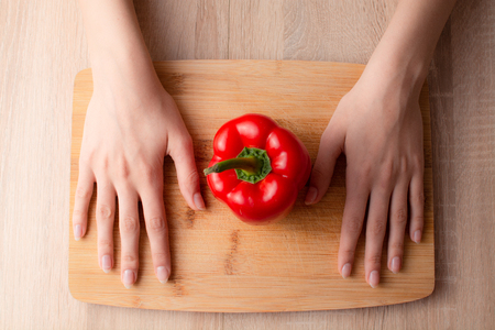 Womens hands, knife and a Bell pepper on the wooden cutting board Stok Fotoğraf