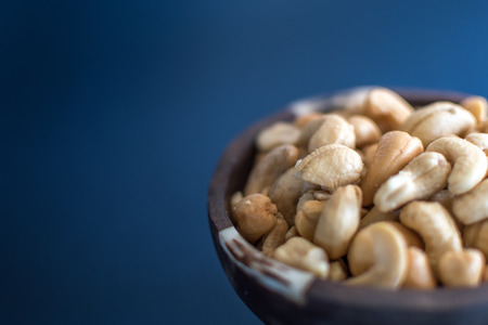 A bowl of cashew nuts on blue background