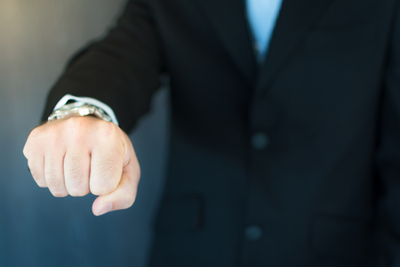 A young executive extending his arm and fist pumping