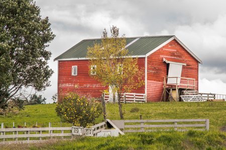 a view of a beautiful deserted red old barn Imagens