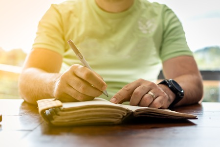 A young successful person taking notes in a personal journal Imagens