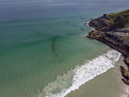 A beautiful drone photo of a surfer waiting for a wave at Puheke beach in the Karikari peninsula, Far North of New Zealand