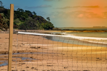 A volleyball net on the beach at sunset Imagens