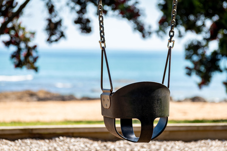 An empty swing at a playground by the sea